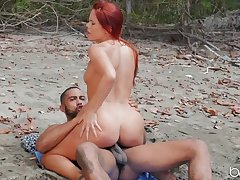Sultry redhead makes love with Ebony guy on the beach